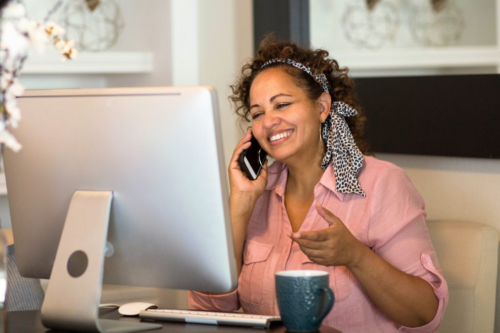 older woman sitting at home office on phone in front of computer